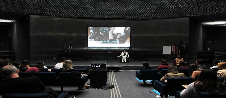 Foto do auditório da Secretaria de Estado dos Direitos da Pessoa com Deficiência de São Paulo. Em primeiro plano, alunos sentados em poltronas. Ao fundo, no palco do auditório, a gestora do Programa Moda Inclusiva, Izabelle Palma.