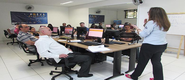 Foto da sala de aula. Onze usuários sentados em frente aos computadores e uma técnica em pé.