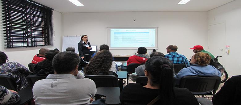 Foto da sala de aula. Em primeiro plano, 15 usuários sentados em cadeiras pretas. Ao fundo, uma técnica em pé.