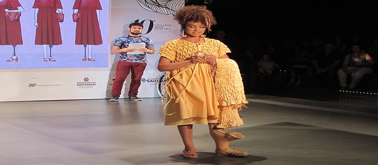 Foto de modelo com deficiência desfilando com vestido amarelo.