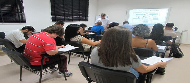 Foto da sala de aula. Em primeiro plano, 12 usuários sentados em cadeiras pretas. Ao fundo, um técnico em pé.