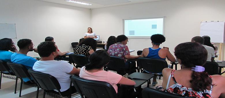Foto da sala de aula. Em primeiro plano, treze usuários sentados em cadeiras pretas. Ao fundo, a técnica em pé e uma lousa interativa.