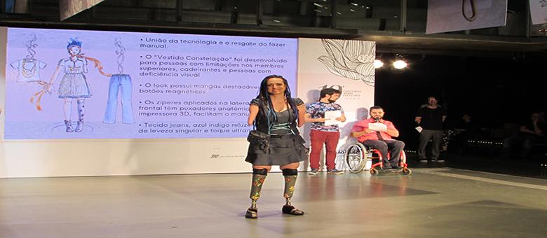 Foto de modelo com deficiência física desfilando com um vestido jeans.