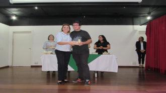 Foto de um usuário com certificado na mão, ao lado da técnica Fabiana.