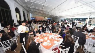 Vista longitudinal do terraço, com as mesas dispostas em fileiras, e ao fundo o palco de apresentação. Em primeiro plano garçom servindo suco de laranja, para pessoas sentadas em uma das mesas, que conversam entre si, e, ao fundo um grupo preparando a apresentação do prêmio.