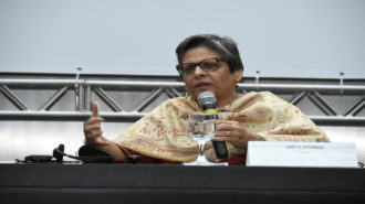 Foto da palestrante Amita Dhanda falando ao microfone.