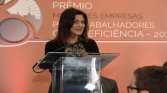 Foto da Prof.ª Lúcia França (Primeira-dama do estado de São Paulo) em pé, apoiada no púlpito de acrílico, falando ao microfone. Lúcia veste botas de cano alto, uma saia longa na cor verde, blusa estampada e um casaquinho curto na cor preta.
