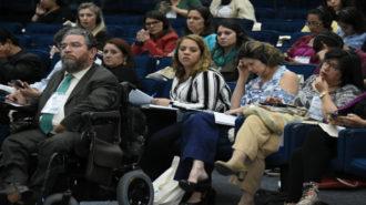 Foto dos convidados sentados em poltronas azuis no auditório da Secretaria.