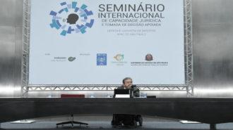 Foto do palestrante Carlos Rios Espinosa falando ao microfone, na mesa.