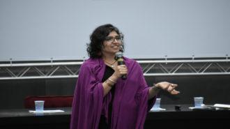 Foto da palestrante Andrea Parra falando ao microfone, em pé, no palco.