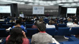 Foto do auditório da Secretaria. Em primeiro plano, pessoas sentadas em poltronas azuis. Ao fundo, a palestrante Andrea Parra falando ao microfone, em pé.
