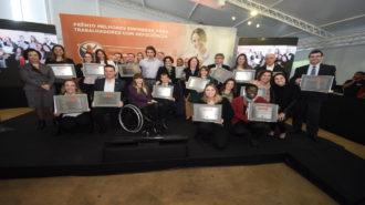 Foto conjunta com todos os representantes das empresas premiadas com suas respectivas placas e ao fundo o painel do V Prêmio Melhores Empresas para Trabalhadores com Deficiência.