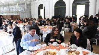 Sobre a mesa onde três pessoas preparam seu café com leite, duas cestas de pães, copos, xícaras, talheres e guardanapos, ao redor, outras mesas, fotógrafos, filmadoras e outros participantes do prêmio.