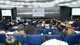 Foto ampliada do auditório da Secretaria. Em primeiro plano pessoas sentadas nas poltronas azuis do auditório e à frente, na mesa o Prof. Luiz Davi Alberto Araújo falando ao microfone.