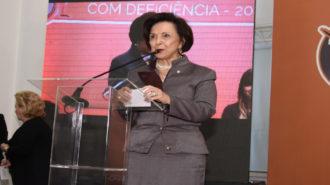 Foto da Dra. Linamara Rizzo Battistella (Secretária de Estado dos Direitos da Pessoa com Deficiência), vestindo um tailleur na cor cinza (casaco e saia), botas de cano curto, em pé, apoiada em um púlpito de acrílico, e, ao microfone, realizando a abertura do evento.