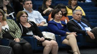 Foto da Dra. Linamara Rizzo Battistella (Secretária de Estado dos Direitos da Pessoa com Deficiência de São Paulo) sentada ao lado de outros convidados no auditório.