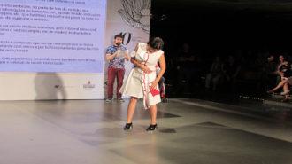 Foto de modelo desfilando com vestido branco com detalhes vermelhos.