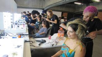 Foto de modelos e estilitas sendo maquiadas e arrumando o cabelo no camarim.