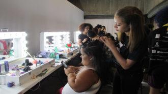 Foto de modelo arrumando o cabelo no camarim do evento.