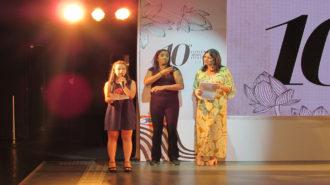 Foto de uma das modelos falando ao microfone. Ao fundo, a apresentadora do evento e a intérprete de Libras.