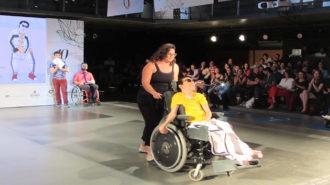 Foto de modelo com deficiência física vestindo camiseta amarela e calça branca.