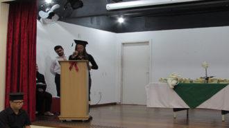 Foto do auditório do Centro de Tecnologia e Inovação. Em primeiro plano, adolescente sentado. Ao fundo, o palco, um técnico e uma usuária falando ao microfone.