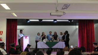 Foto do auditório. Em primeiro plano, pessoas sentadas. Ao fundo, o palco, um técnico falando ao microfone atrás do púlpito e outros técnicos atrás de uma mesa com certificados.