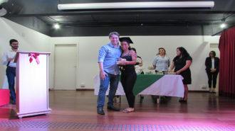 Foto de uma usuária com certificado na mão, ao lado do técnico Fernando.