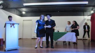 Foto de um usuário com certificado na mão, ao lado da técnica Fabiane.