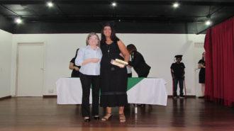 Foto de uma usuária com certificado na mão, ao lado da técnica Cristina.