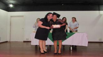 Foto de uma usuária com certificado na mão, ao lado da técnica Alessandra.