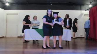 Foto de uma usuária com certificado na mão, ao lado da técnica Chimenia.