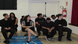 Foto de oito adolescentes do curso Laboratório de Imagem sentados em cadeiras pretas.