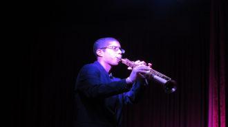Foto de um adolescente tocando saxofone.