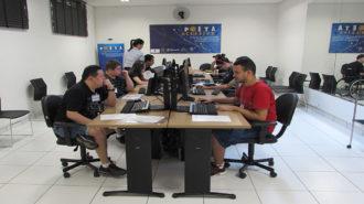 Foto de usuários sentados em cadeiras pretas, em frente aos computadores. Ao fundo, o banner do Programa POETA e uma técnica em pé.