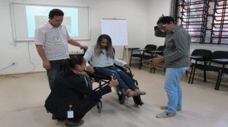 Foto de uma usuária sentada em uma cadeira de rodas preta, dois usuários em pé e uma técnica abaixada perto da cadeira.