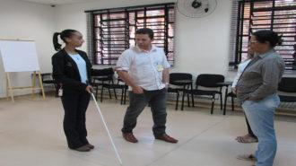 Foto de uma técnica e três usuários. A técnica segura uma bengala e o braço do usuário. Outras duas usuárias estão, em pé, olhando para eles.
