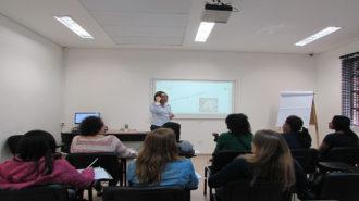 Foto da sala de aula. Em primeiro plano, usuários sentados em cadeiras pretas. Ao fundo, uma técnica, em pé.