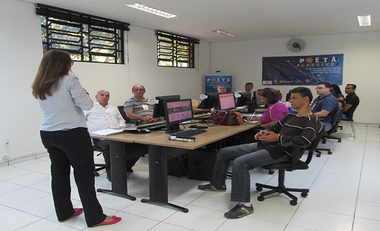 Pessoas sentadas em frente aos computadores no curso Educação Econômica e Financeira.