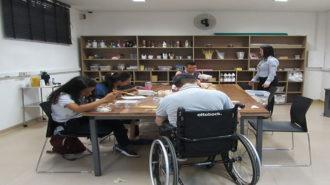 Foto da sala de artes do Centro de Tecnologia e Inovação. Quatro usuários sentados próximos a uma mesa grande. Ao fundo, um armário com várias prateleiras e uma técnica. Os usuários estão colando pedaços de papel em caixas pequenas.