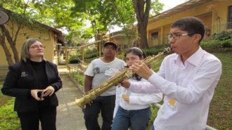 Foto de três usuários e uma técnica. Um dos usuários está tocando saxofone.