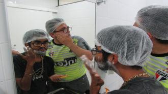 Foto de dois usuários, em frente ao espelho, passando creme de barbear.