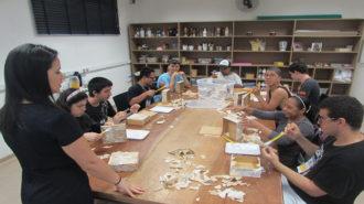 Foto da sala de artes do Centro de Tecnologia e Inovação. Nove usuários sentados próximos a uma mesa grande e uma técnica em pé. Os usuários estão colando pedaços de papel em caixas pequenas.