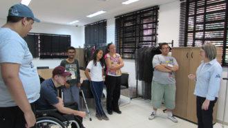 Foto da sala de aula. Cinco usuários em pé e um na cadeira de rodas conversando com a técnica.