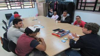 Foto da sala de aula. Oito usuários e um técnico sentados próximos a uma mesa. Os usuários estão jogando um jogo de tabuleiro.