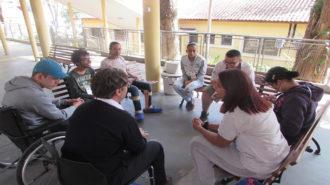 Foto do pátio do Centro de Tecnologia e Inovação. Sete usuários e um técnico estão sentados e conversando.