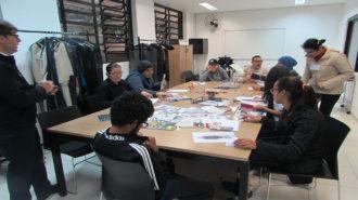 Foto da sala de aula. Nove usuários sentados próximos a uma mesa, fazendo recorte. Um técnico acompanha a atividade, em pé.