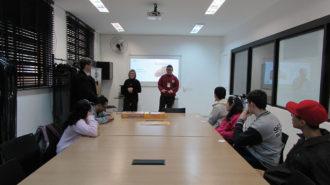 Foto da sala de aula. Seis usuários sentados próximos a uma mesa e dois técnicos e um usuário em pé. Os usuários participam de uma atividade de mímica.