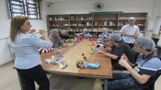Foto da sala de artes do Centro de Tecnologia e Inovação. Oito usuários sentados próximos a uma mesa grande e dois técnicos em pé. Os usuários participam de uma atividade de auto higiene. Sobre a mesa utensílios de limpeza e espelhos.