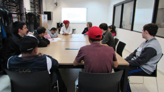 Foto da sala de aula. Dez usuários e uma técnica sentados próximos a uma mesa, conversando.